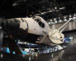2013年6月7日在佛羅里達州肯尼迪航天中心展廳亞特蘭蒂斯號航天飛機有效載荷艙門打開,伸出機械臂。亞特蘭蒂斯置於30英尺(9.1米)高處,並以43.21度角傾斜,彷彿繞地球運行(AFP PHOTO/Bruce Weaver)