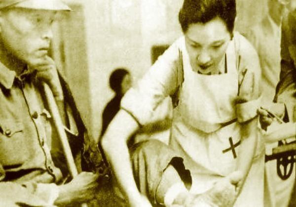 1938年宋美龄在战区为抗日受伤战士包扎伤口。(法新社)