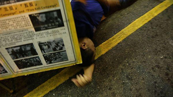 有香港市民不滿林國安等人所為,衝破封鎖線,有市民被林勒住脖子,又遭另一惡徒用腳狠踢,混亂中林跌倒在地。(攝影:潘在殊/大紀元)