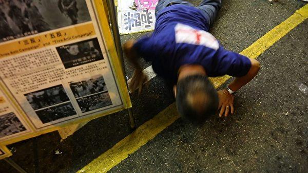 有香港市民不滿黑幫青關會頭目林國安等人所為,衝破封鎖線,該香港市民被林勒住脖子,又遭另一惡徒用腳狠踢,混亂中青關會頭目林國安跌倒在地,引起周圍香港人鼓掌叫好。(攝影:潘在殊/大紀元)