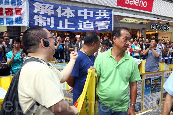 一名市民進入警戒線內,對青關會惡徒示不文手勢表達不滿。旁邊的市民歡呼拍掌。(攝影:潘在殊/大紀元)