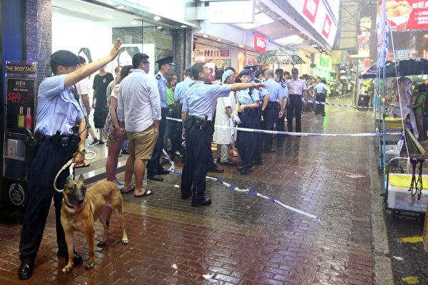 由于中共江泽民集团的的走狗梁振英的垂死挣扎,香港青关会恶徒7月14日再次暴力骚扰位于旺角行人专用区的法轮功真相点,上演了一场正邪大战;大批市民纷纷怒斥青关会的中共邪恶行径以及警方的纵容,图为警方在发生冲突后出动警犬维持秩序。(摄影:潘在殊/大纪元)