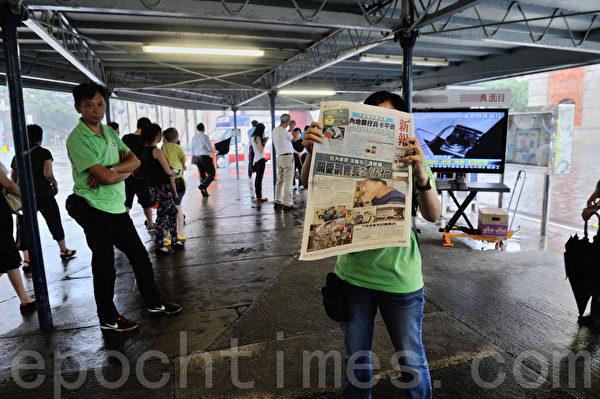 7月14日,香港市民上街頭包圍青關會頭目,聲援法輪功事件觸碰中共神經。一直被媒體報導有黑道背景的香港富商楊受成控制的《新報》居然公開製造假新聞,編造假新聞來構陷法輪功學員,圖為青關會在香港尖沙咀派發造假抹黑法輪功內容的《新報》,煽動仇恨。(攝影:宋祥龍/大紀元)