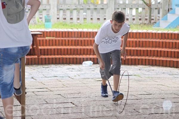 凯拉塔里民俗舞蹈团小朋友体验,滚铁圈是利用一根长长的铁钩推动铁圈往前滚动,要用点小技巧才能顺利完成。(摄影:曾汉东/大纪元)