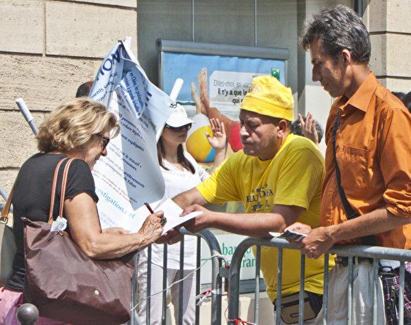 過往民眾簽名支持法輪功學員反迫害。(攝影:關宇寧/大紀元)