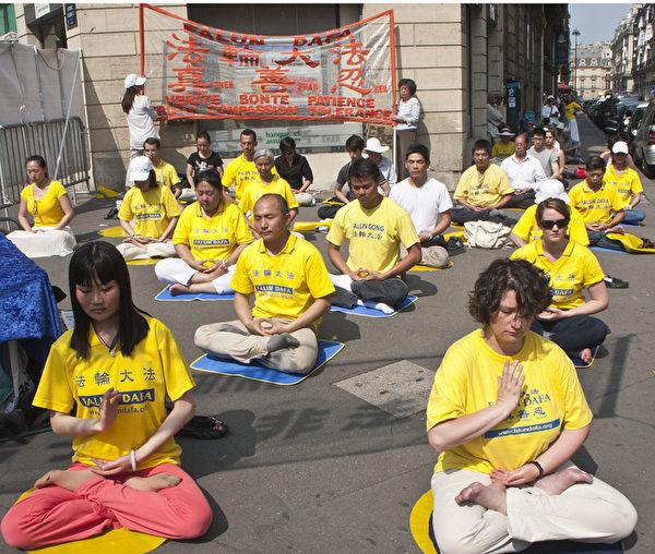法輪功學員在巴黎中共駐法國大使館對面集會、煉功,呼籲社會各界關注並共同制止中共對法輪功學員長達14年的打壓和殘酷迫害。(攝影:關宇寧/大紀元)