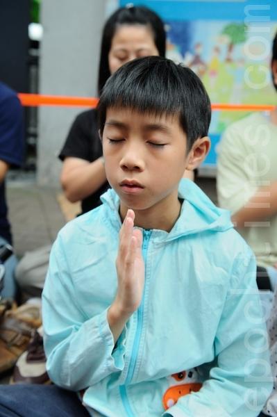 一名法輪功小學員正在靜坐(攝影:宋祥龍/大紀元)