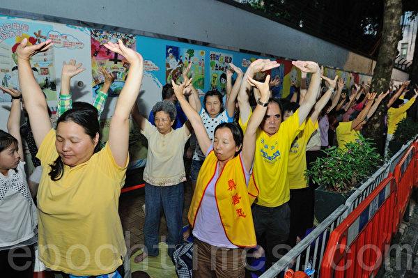 香港法輪功學員在中聯辦後門對面馬路集會,平和演示法輪功的五套功法。(攝影:宋祥龍/大紀元)