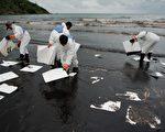泰國PTT全球化學公司因海底輸油管破裂,導致沙美島普勞海灘遭原油汙染。圖為石油公司派遣人力在現場清理油汙。(Nicolas ASFOURI/AFP)