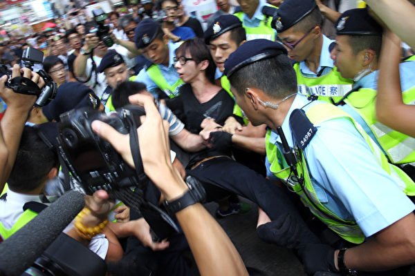 「香港人優先」成員招顯聰被大批警員包圍和抬走。(潘在殊/大紀元)