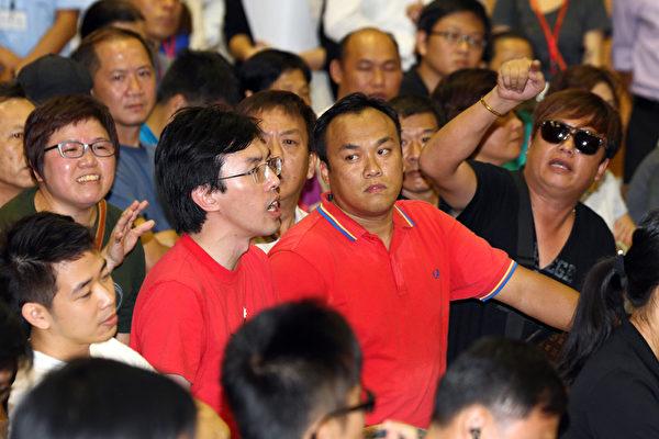 香港特首梁振英8月11日到天水围出席地区论坛,多个政党和团体到场示威抗议,批评梁振英将香港中共黑道化,应该尽早下台,图为会场内(左一红衫者)社民连副主席吴文远被梁振英的支持者左右包围,其中旁边红衫者为场内外黑社会人士的指挥者陈嘉辉。(潘在殊/大纪元)