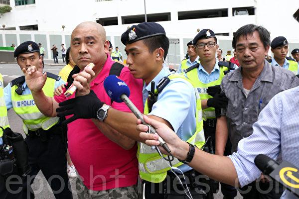香港特首梁振英8月18日再次落區到觀塘出席論壇,各個政黨團體過千人到場抗議,圖為兩名梁振英的支持者涉嫌毆打抗議人士被捕。(潘在殊/大紀元)