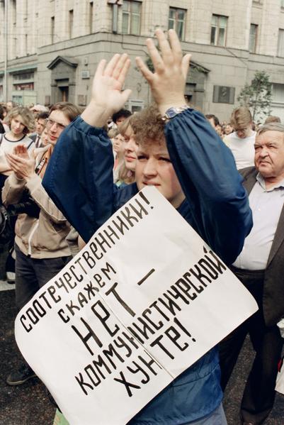 """1991年8月20日,一个苏联妇女咬着""""没有共产党军政府""""海报。(DIMA KOROTAYEV / AFP)"""