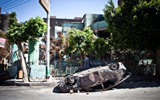 埃及军方与穆斯林兄弟会经过数百人死亡的流血冲突之后,关系到中东稳定的西奈半岛8月19日传出24名警察在埋伏袭击中死亡。图为18日街道上行人经过一台已烧焦的汽车旁边。(VIRGINIE NGUYEN HOANG/AFP)