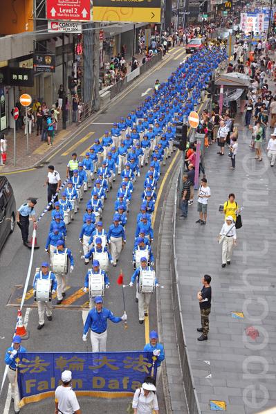 香港國殤日的集會結束後,800名遊行人士手持各式橫幅幡旗,從北角英皇道遊樂場出發前往中共駐港聯絡辦事處,浩浩蕩蕩的遊行隊伍吸引大批中港人士駐足觀看。(潘在殊/大紀元)