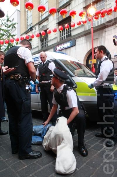 """伦敦唐人街法轮功讲真相劝""""三退""""活动再遭暴徒袭击,肇事者被警方带走。(摄影:冠齐/大纪元)"""