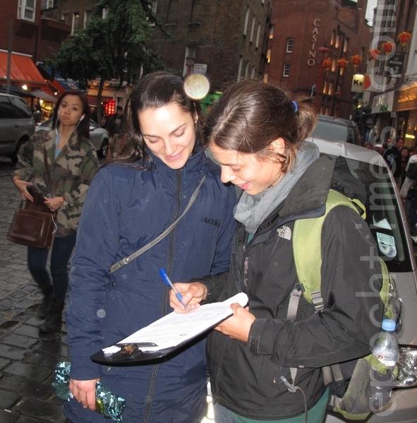 2013年9月15日,两个西班牙女孩明白法轮功真相后,在制止中共活摘法轮功学员的请愿书上签名。(摄影:肖民/大纪元)
