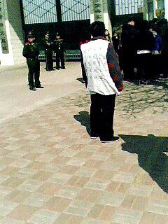 周向陽的老母親穿狀衣鳴冤(圖片來源:明慧網)