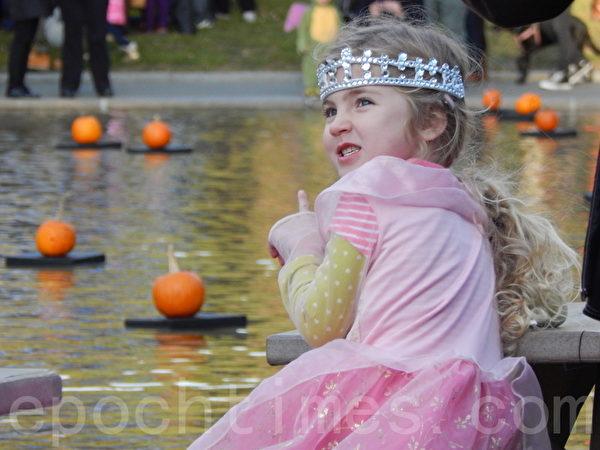 小女孩打扮成公主模样开心看南瓜。(摄影﹕杨天仪/大纪元)