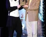 纪佳松(左)发行新专辑《梦游》,爸爸纪明阳送上曾经制作百万专辑的歌曲奖牌,希望儿子新专辑一样能有好成绩。(丘普林/大纪元)