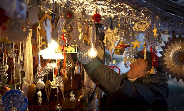 民众在慕尼黑的圣诞市场中挑选商品。作为德国圣诞传统中重要的一部分,销售热葡萄酒、果子蛋糕和圣诞树装饰品等节日必备的圣诞市场在全德范围内开张。(Joerg Koch/Getty Images)