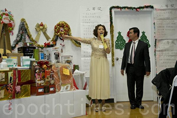 希望之声的总裁曾勇(右)和FM92.3台长高洁向来宾介绍晚会奖品。(曹景哲/大纪元)