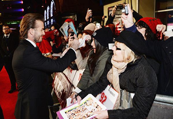 12月1日,曼联纪录片《92班》在全球首映式,大卫•贝克汉姆(左)给粉丝签名。(Dave J Hogan/Getty Images)