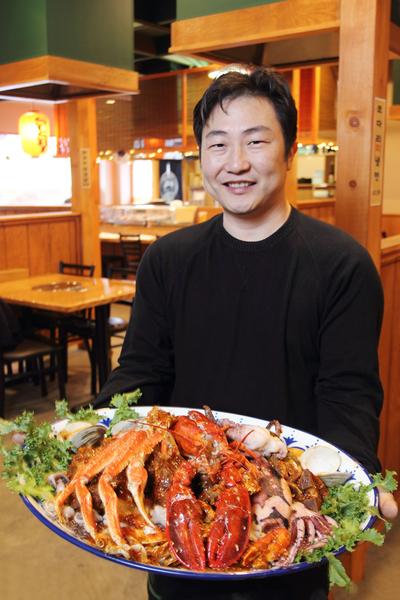 老板金官燮先生和他奉獻給中國朋友的超大盤「海鮮豬排盅」。(攝影:張學慧/大紀元)
