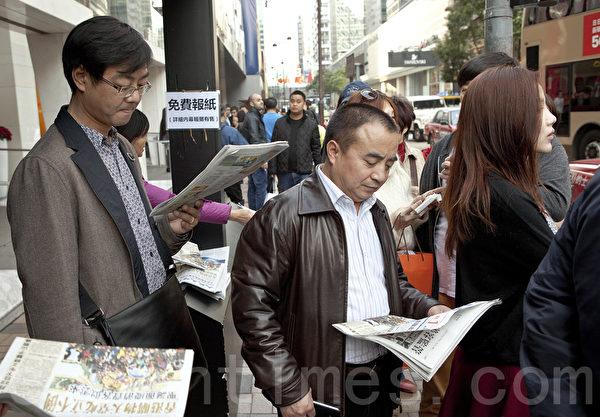 聖誕期間大批大陸遊客來港購物之餘,也都爭相觀看大紀元時報的最新時局報導,把真相也帶回家。(余鋼/大紀元)