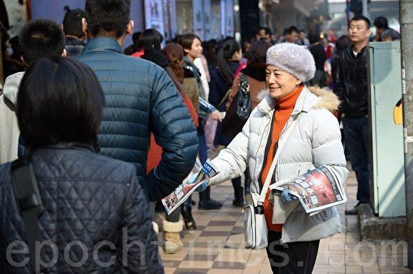 新年將近,許多大陸人來港購物,經過海港城廣東道爭拿大紀元報紙。(宋祥龍/大紀元)