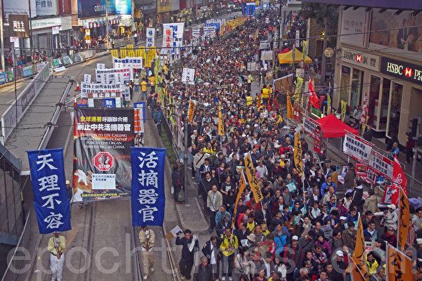 香港民间人权阵线举行的2014年新年大游行,3万人参加,法轮功的游行队伍以雄壮的天国乐团演奏和各式揭露中共迫害和退党的幡旗横额,成为最受瞩目的阵列。(潘在殊/大纪元)