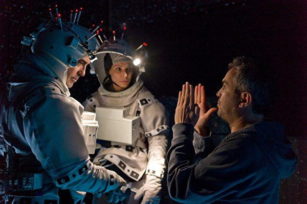 《地心引力》导演阿方索•柯朗在给乔治•克鲁尼和桑德拉•布洛克说戏。(华纳兄弟提供)