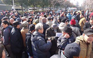 1月22日,上海市政府門前聚集近千人抗議。當時,上海電視臺的2輛採訪車因不是關注訪民的冤情,被憤怒的訪民團團圍住。(知情者提供)