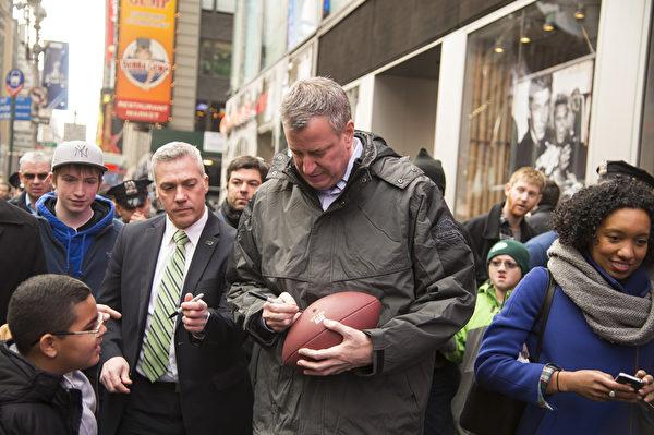 紐約市長白思豪(Bill de Blasio)攜夫人Chirlane McCray and 兒子Dante de Blasio 訪問超級盃大道( Super Bowl Boulevard)。爲小球迷簽名。(戴兵/大紀元)