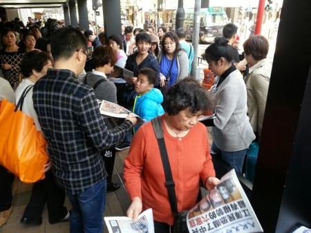 中国新年期间,大批大陆游客挤爆香港。他们街头巷尾拿大纪元阅读,成为香港一大特殊景象。(大纪元图片)