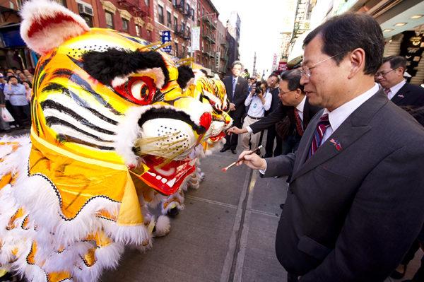 凡新獅初舞,按照傳統的俗規,要舉行「點睛」儀式。主人會邀請德高望重的主禮嘉賓一起,用新筆把硃砂塗在獅的眼睛上,象徵給予生命。點睛人把執筆的手揚起時,全場鼓聲雷鳴,鑼聲大響,一片歡騰景象。圖為在2010年華埠慶中華民國99年雙十愛國大游行之前,舉行了熱鬧的舞虎的點睛儀式,時任中華公所主席的伍權碩和時任經文處處長的高振群為老虎點睛,預祝華人虎年吉祥、虎虎生風。(攝影:戴兵/大紀元)