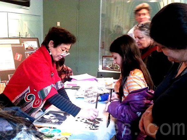 大年初二,在费城独立海港博物馆举行的庆祝中国新年活动上,蔡周文涟女士正在教小朋友使用毛笔写字作画。(韩林/大纪元)