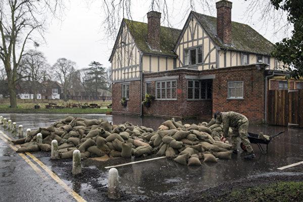 2014年2月12日,英國部份地區連日降雨,泰晤士河沿岸多地決堤。圖為士兵準備沙袋防洪。 (Oli Scarff/Getty Images)