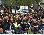 近五百位新聞工作者、民主及建制派立法會議員、市民、新聞系學生身穿黑衣3月2日在中午12點齊集在添馬公園草地,出席由記協舉行的「新聞界-企硬-反暴力-默站行動」,他們在一幅寫著「They can」t kill us all」巨型橫幅上寫下對明報前總編輯劉進圖的祝福。他們放下手上的相機、筆記部等採訪工具,默站五分鐘,以示對劉進圖先生遇襲的傷感、不滿。(潘在殊/大紀元)