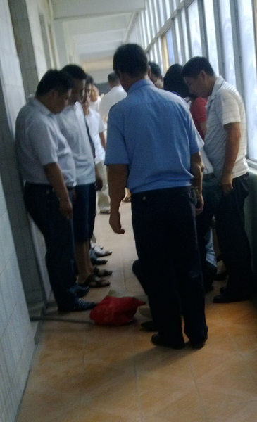 镇政府人员将杜吉阁拖进屋坐在地上遭集体训斥和踢打(作者提供)