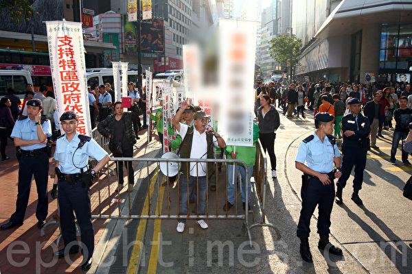 3月23日星期天,青关会再次到法轮功真相点叫嚣闹事,并和市民发生冲突,警方用铁马将他们围困,限制其活动范围。(潘在殊/大纪元)