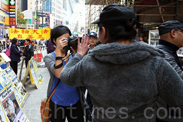 3月23日,路透社女记者到场采访青关会侵扰法轮功真相点,遭青关会恶徒阻挡采访和粗言辱骂,要警员在场保护。(潘在殊/大纪元)