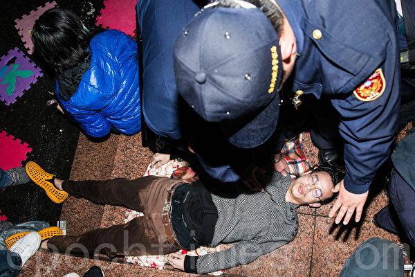 反服貿團體23日晚間闖入行政院,警方24日凌晨開始強制驅離,群眾躺下抵抗。(陳柏州/大紀元)
