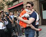 「我不可能把蘇瑞置於我生活之外。」湯姆・克魯斯在法庭陳述中說。圖為2012年7月17日,他抱著女兒蘇瑞現身紐約。(MEHDI TAAMALLAH/AFP)