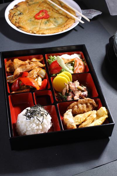 含有米饭、炸饺子、炸鱼饼、沙拉、泡菜、鸡肉、八爪章鱼的特价营养午餐。(张学慧/大纪元)