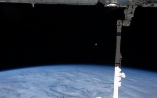 """美国私人航太公司SpaceX与NASA合作后,于2014年4月18日第三度成功发射""""飞龙号"""",运送物资到国际空间站。本图是Hadfield宇航员,在2013年3月27日,从空间站向外拍到月亮升起及""""飞龙号""""与空间站连结的画面。(AFP PHOTO / NASA / Chris Hadfield)"""