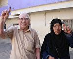 伊拉克4月30日举行国会大选,伊拉克人不顾恐怖份子的死亡威胁,纷纷前往投票所投票。图为一对夫妇在曼苏尔投票所投完票后展示沾有墨水的手指。(KHALIL AL-MURSHIDI/AFP)