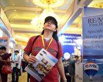 隨著樓市成交量的持續低迷,北京近日出現首個「零首付」促銷樓盤。同時,中共官媒新華網以「樓市絕對危險信號」報導大陸4月份26個大中城市新房價格止漲的消息,顯示大陸房地產市場進入深度調整期。圖為一位女士在5月17日在北京參觀一個國際房地產展覽會。(WANG ZHAO/AFP/Getty Images)