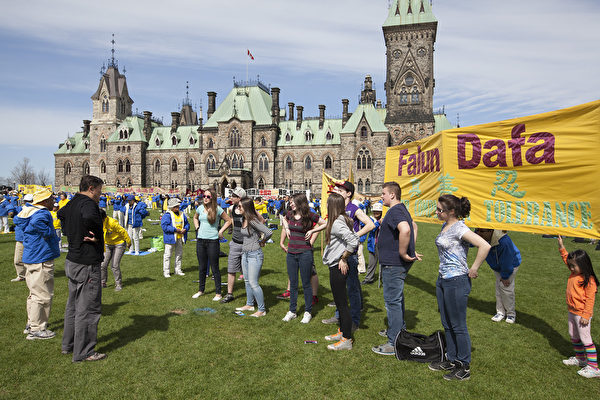 5月7日,來自加拿大東部城市的四百餘名法輪功修煉者匯聚加拿大首都國會山前,慶祝法輪大法洪傳世界22週年。圖為遊客現場學功。(艾文/大紀元)