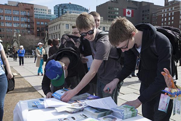 5月7日,來自加拿大東部城市的四百餘名法輪功修煉者匯聚加拿大首都國會山前,慶祝法輪大法洪傳世界22週年。圖為遊客現場簽字制止迫害。(艾文/大紀元)